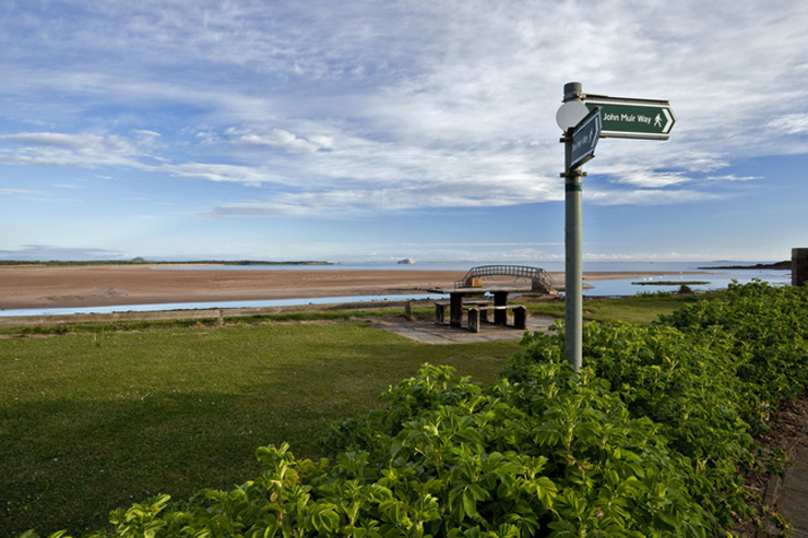 A sign post for the John Muir Way by  Belhaven Bay, with a bridge and the beach in the background.