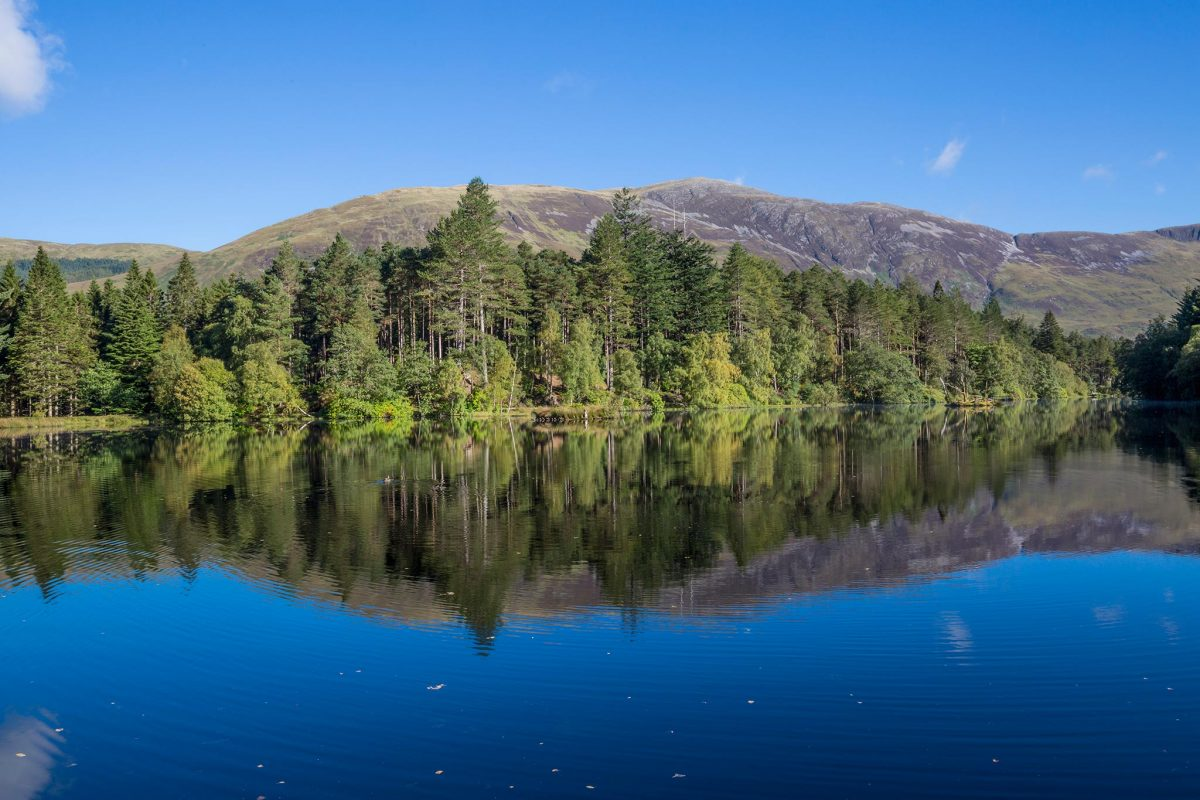 Still water on a Lochan reflects the surrounding woodland and hills