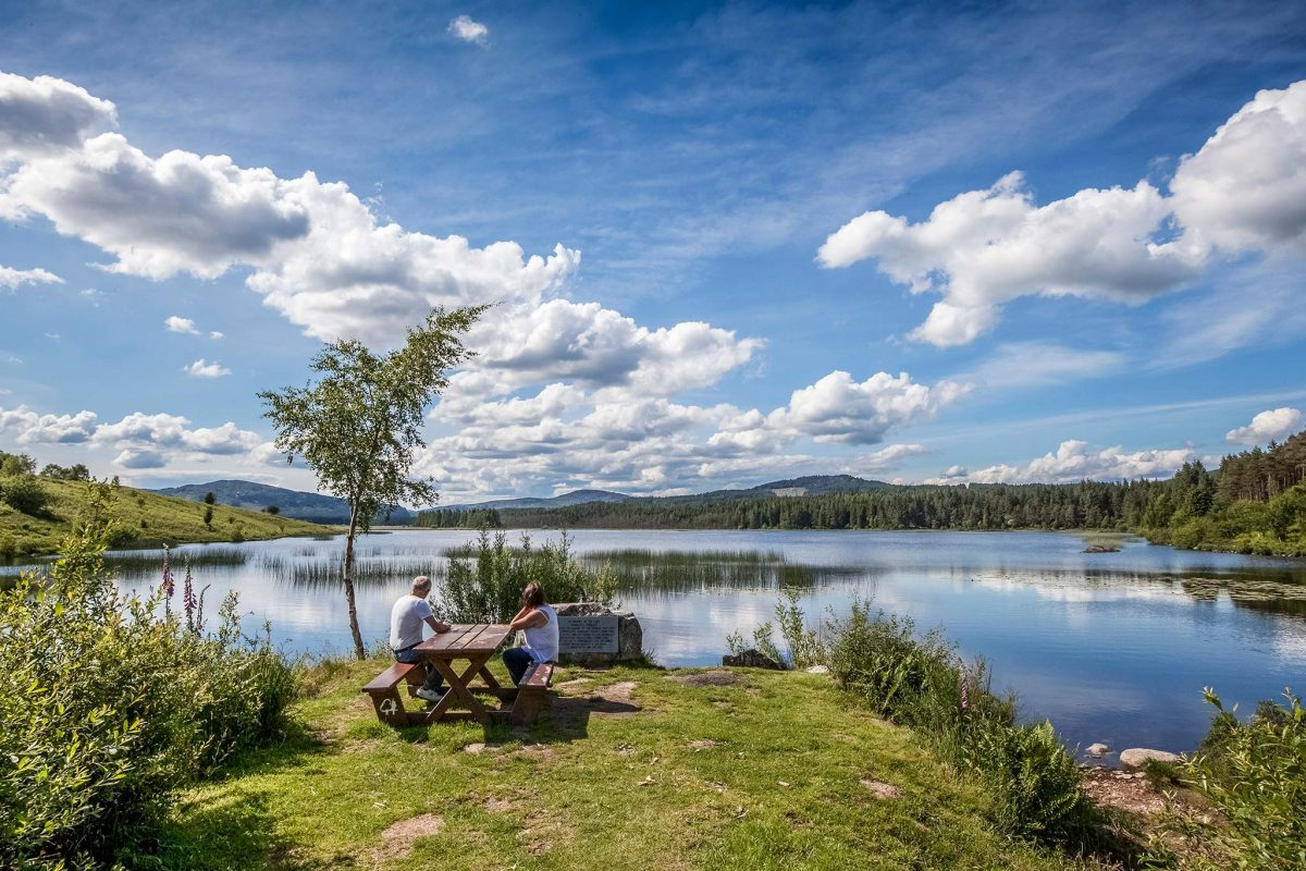A couple sit at a picnic table and look out over the loch.