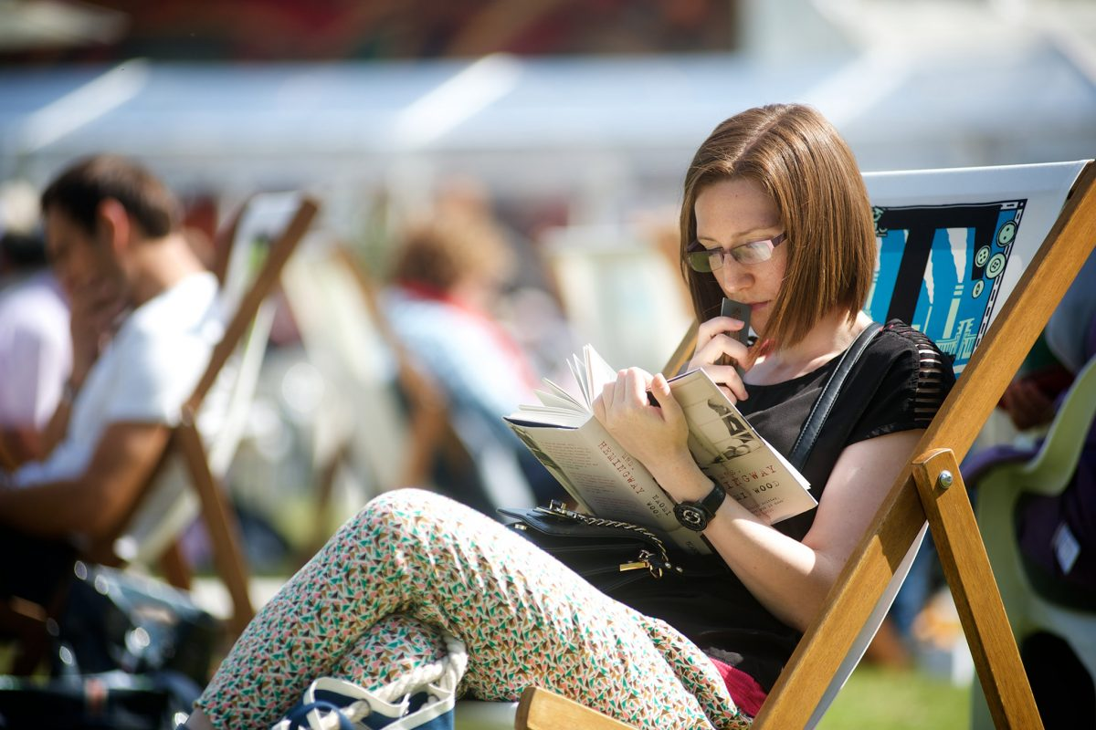 A woman sits on a deck chair reading a book.
