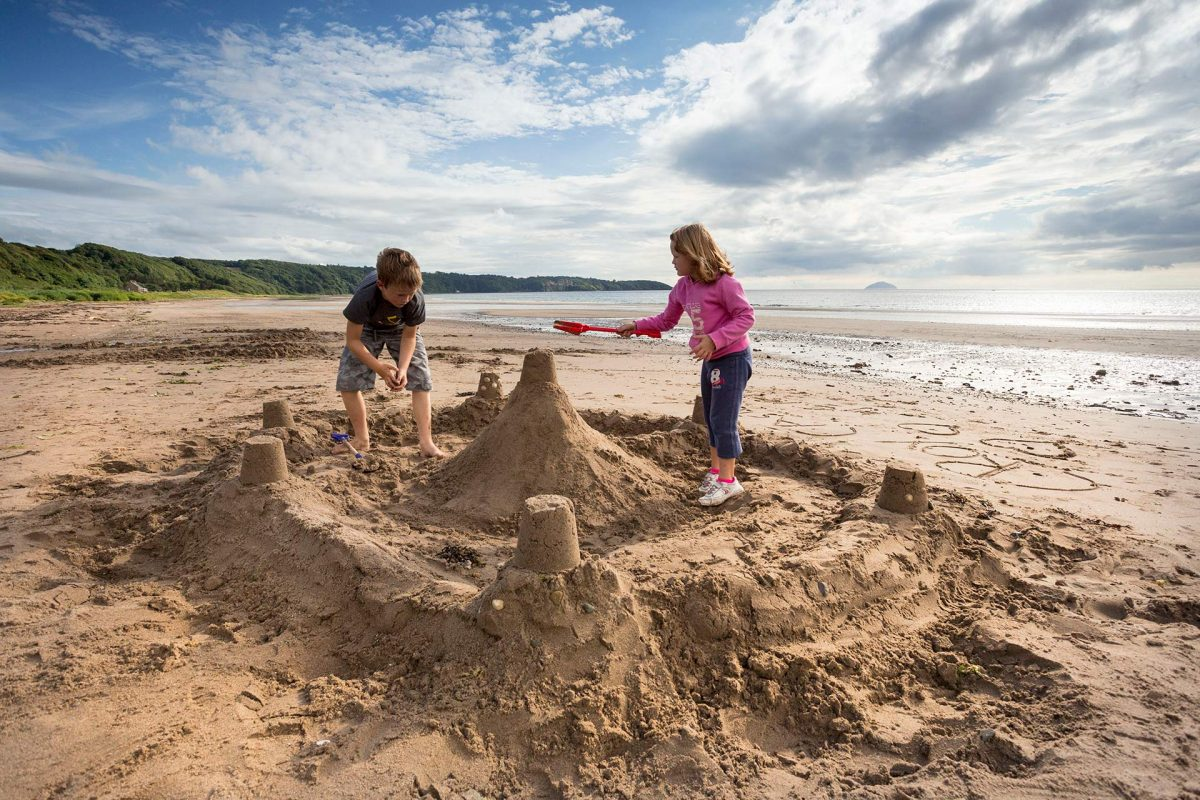 Children building a sandcastle on the beach at Croy Shore, Culzean Bay, with Culzean Castle and Ailsa Craig in the distance, South Ayrshire. Picture Credit : Paul Tomkins