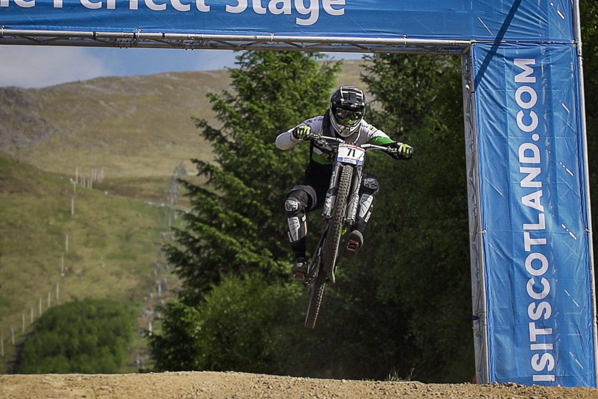A mountain biker in mid air on a jump.