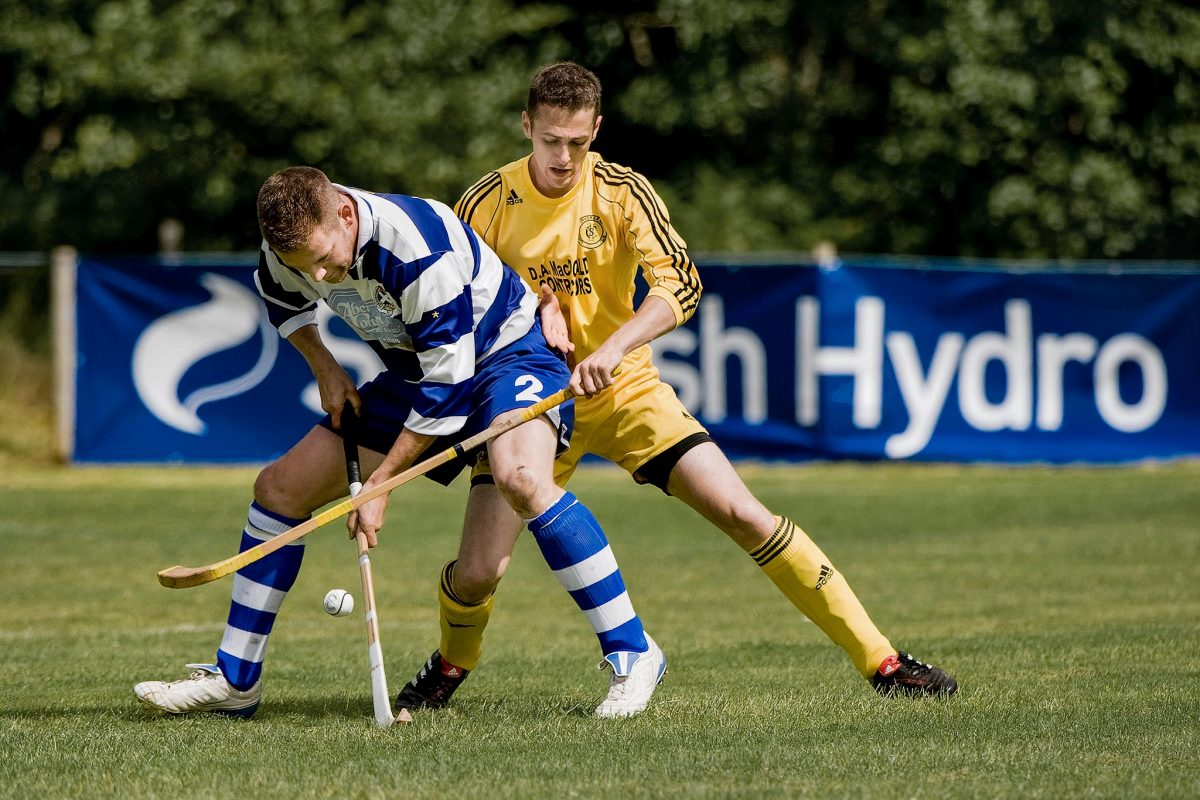 Norman Campbell (Newtonmore) holds off the challenge of Grant Griffin (Inveraray) during the Camanachd Cup semi final at Spean Bridge. 2011