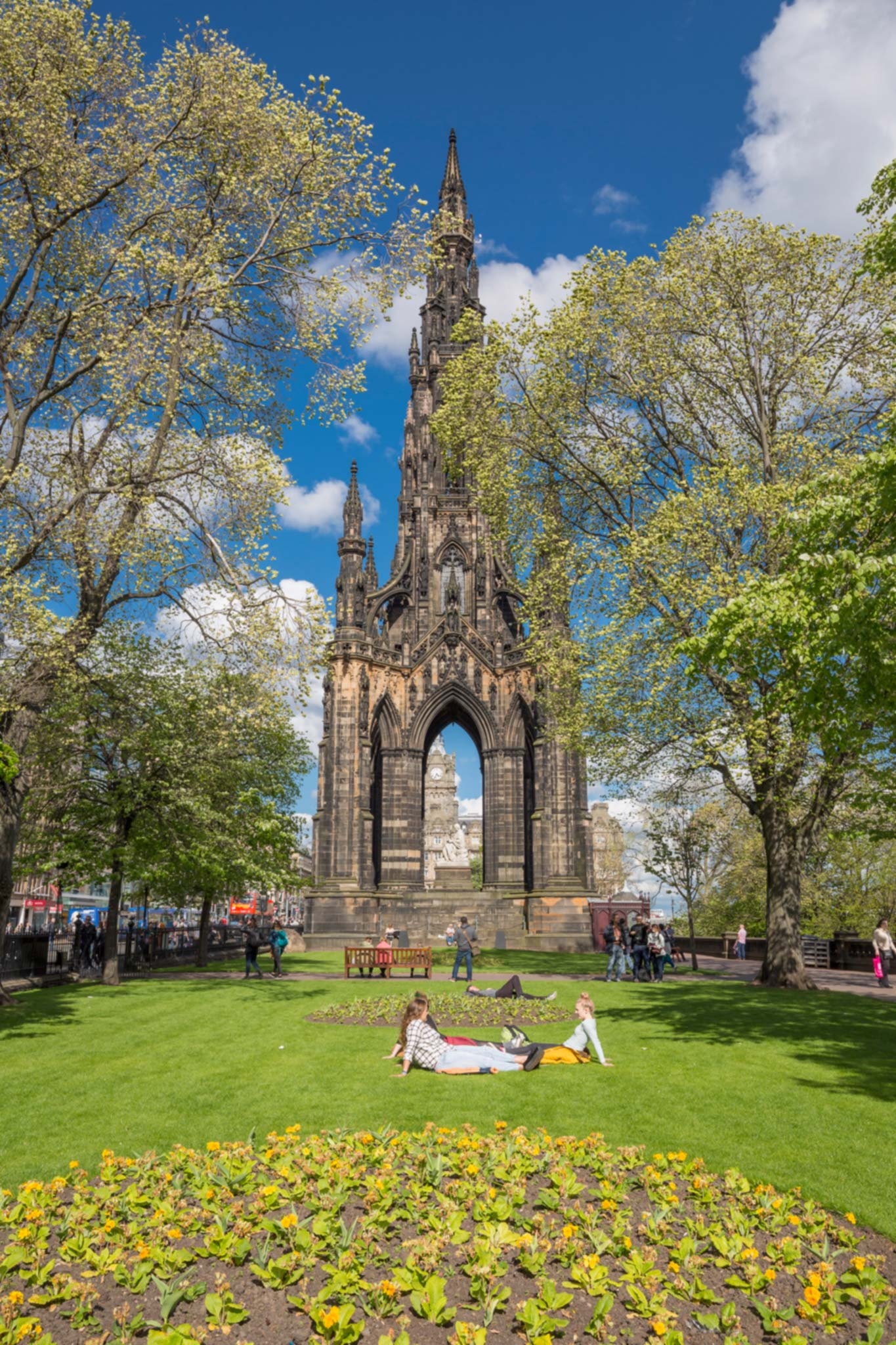 People sunbathe on the lawn in Princes Street Gardens, with Scott Monument in the background