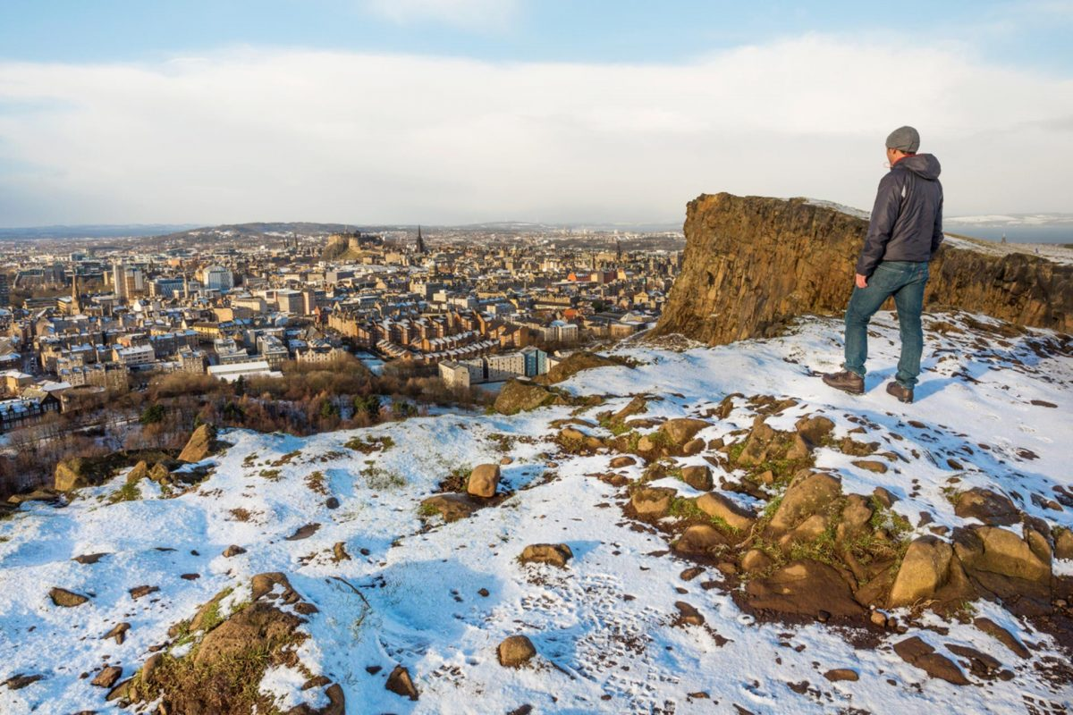 A man stands on Salisbury Crags viewing Edinburgh city.