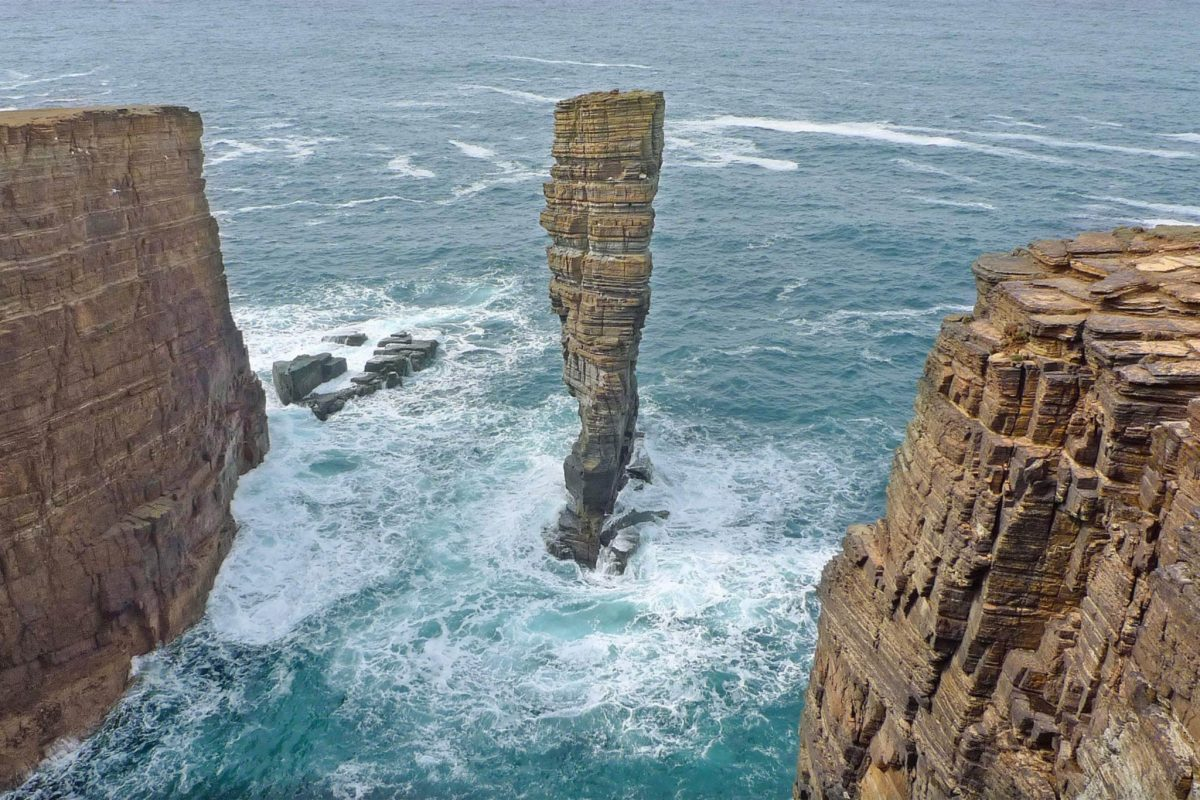 A sea stack stands by cliffs, with raging water below,