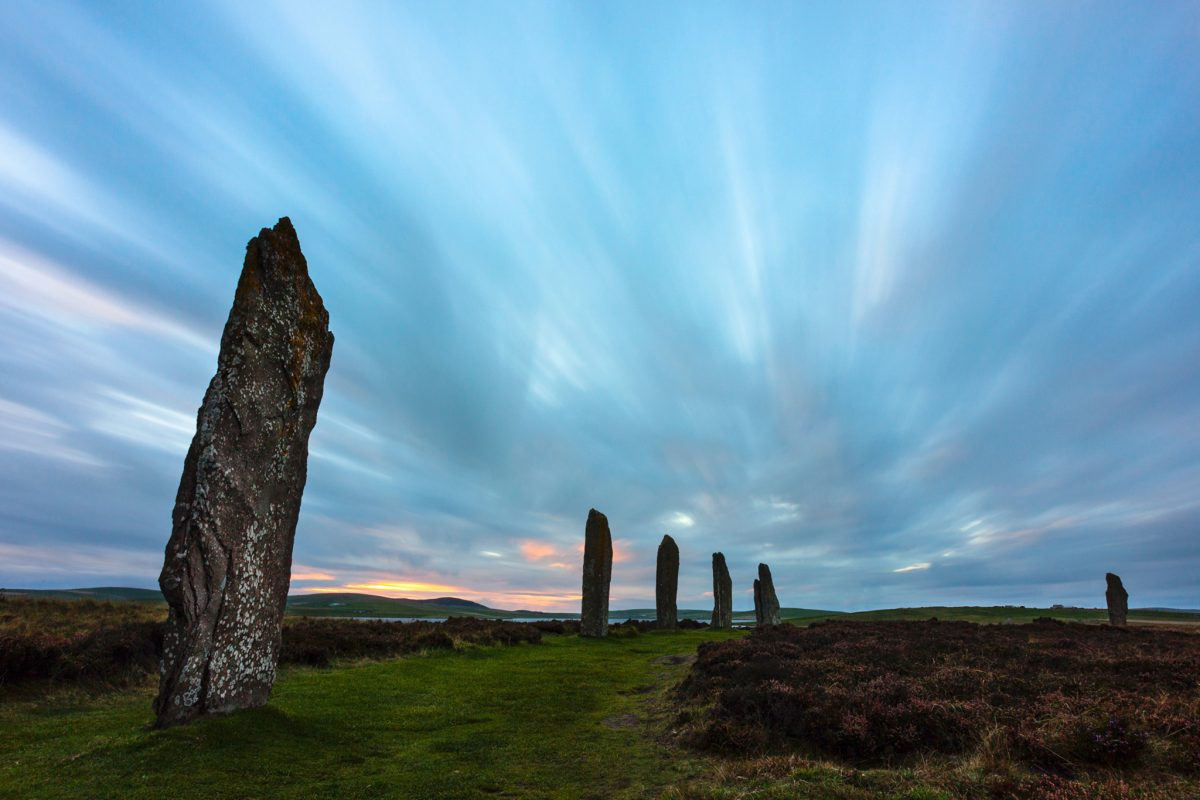 A curved line of standing stones with pink sky in the distance.