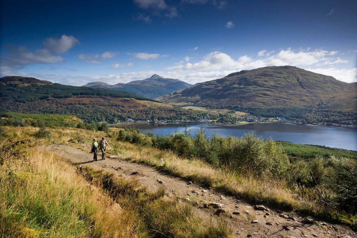 Loch Lomond, A couple walking on a mountain path near Long Long, with Arrochar and Ben Lomond in the distance