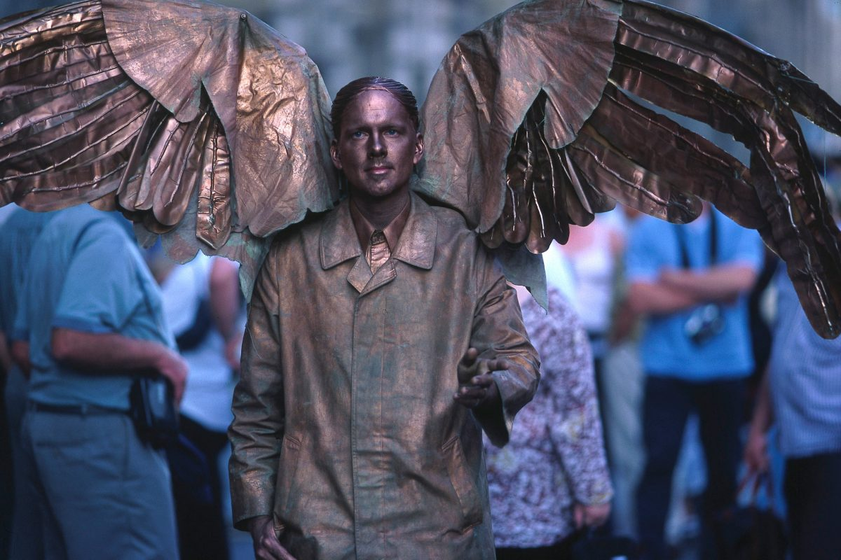 A living statue painted gold with large wings.