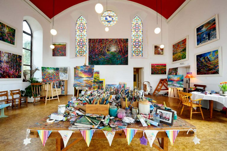 A bright former church is adorned with paintings, with a table of art supplies in the foreground.