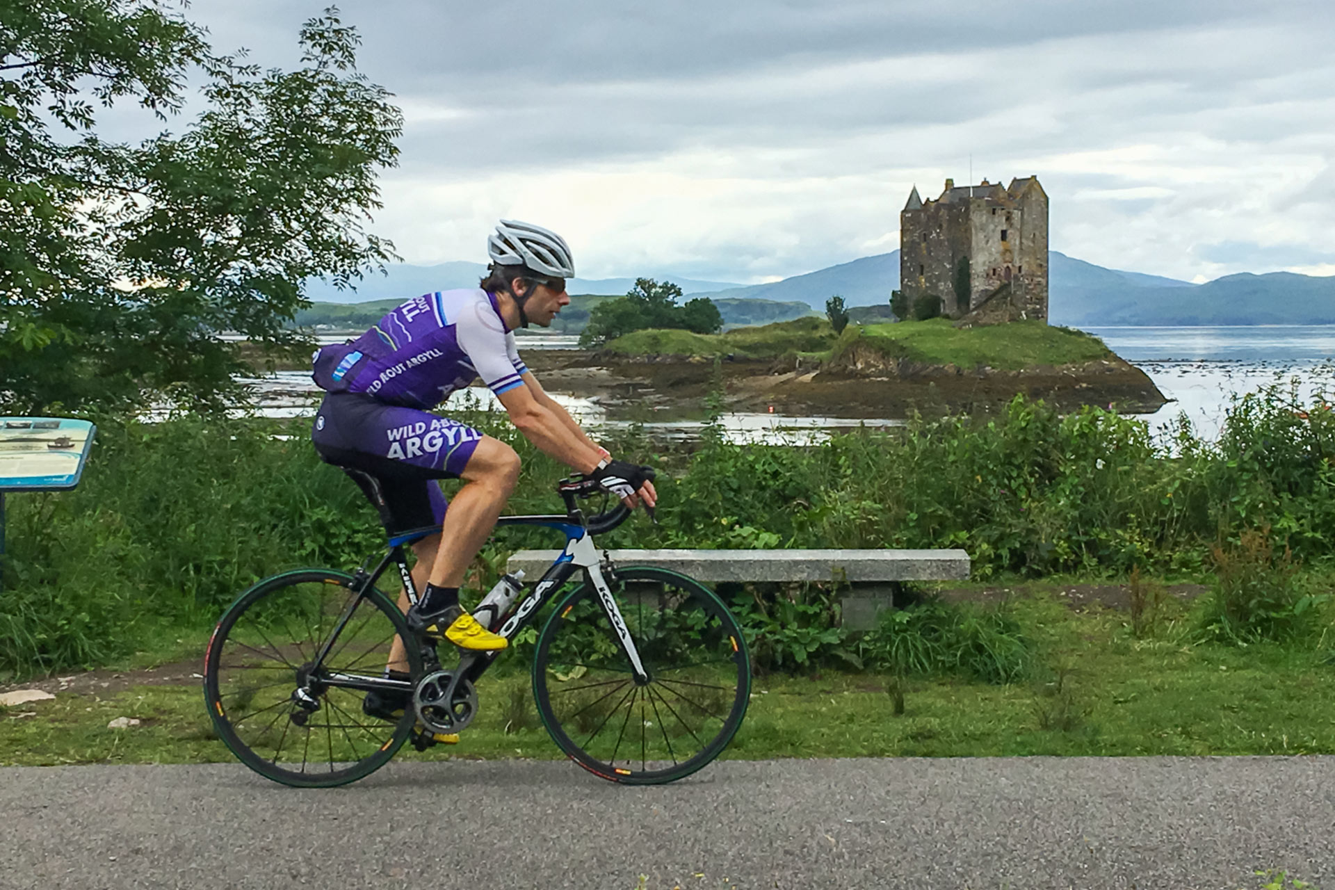 Mark Beaumont cycling along Route 78 in Argyll with Castle Stalker in the background