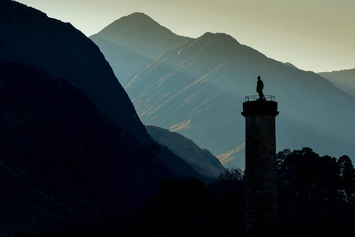 A statue of a kilted soldier on top of a monument, cast into silhouette by the sun, with mountains beyond.