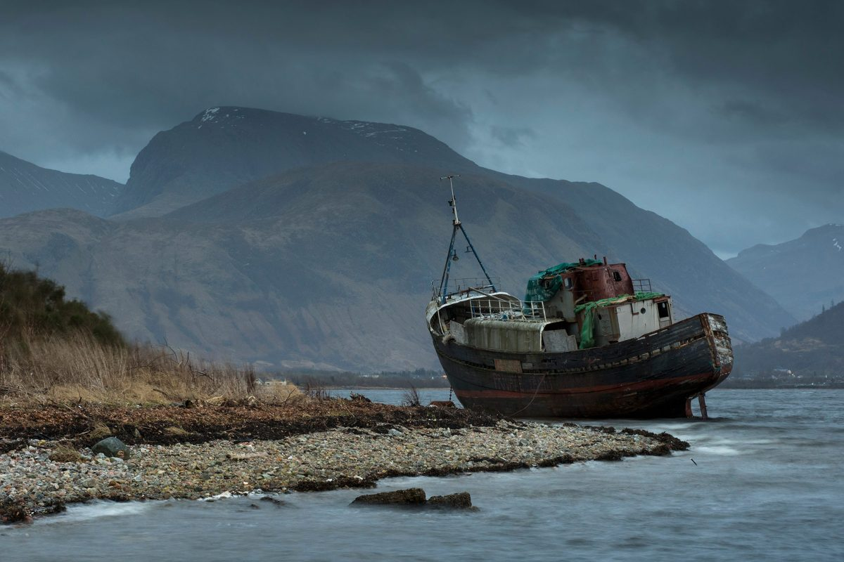 Ben Nevis on a stormy day, with an abandoned boat on the shoreline in the foreground.