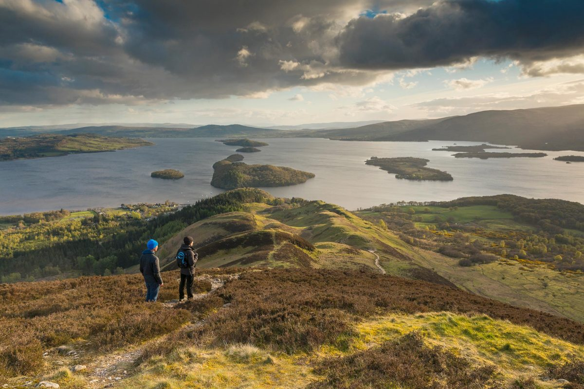 Two hillwalkers admire the view over Loch Lomond from Conic Hill.