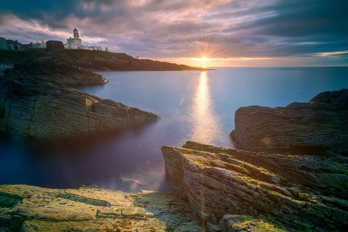 The sun sets over the sea, with the lighthouse in the distance, and cliffs in the foreground.