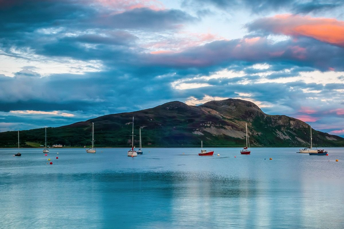 Sailing boats on calm water, with Holy Isle in the background.