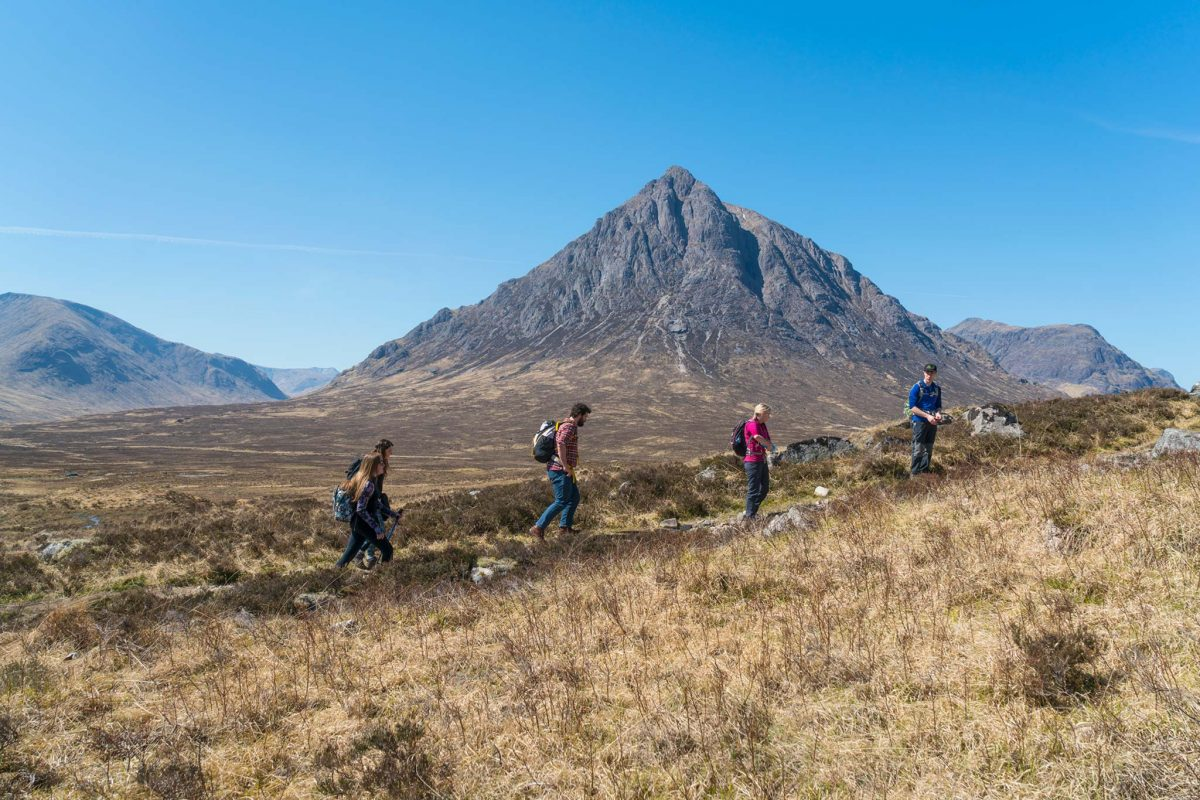 Walkers on the West Highland Way pass the pointed mountain Buachaille Etive Mor.