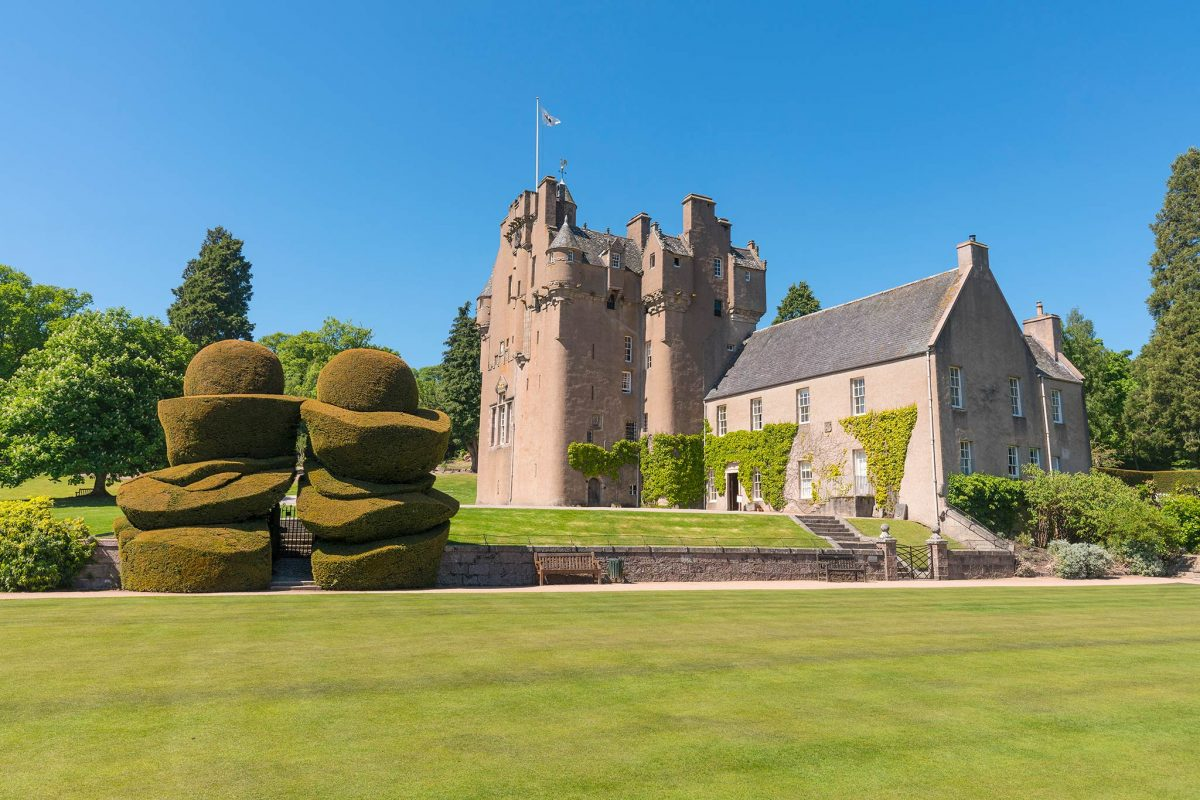 Looking across the lawn to the castle, with large topiary in the foreground.