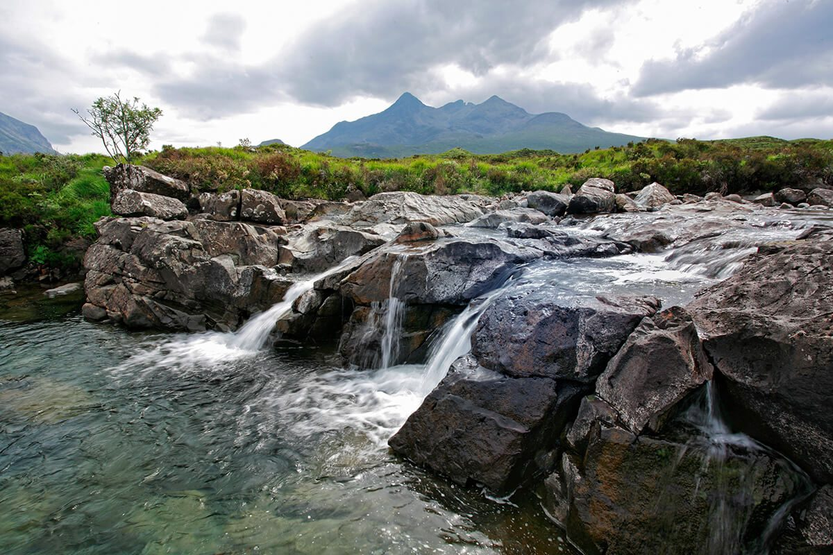 WATERFALL ON SLIGACHAN BURN WITH THE CUILLIN HILL IN THE BACKGROUND ON THE ISLE OF SKYE