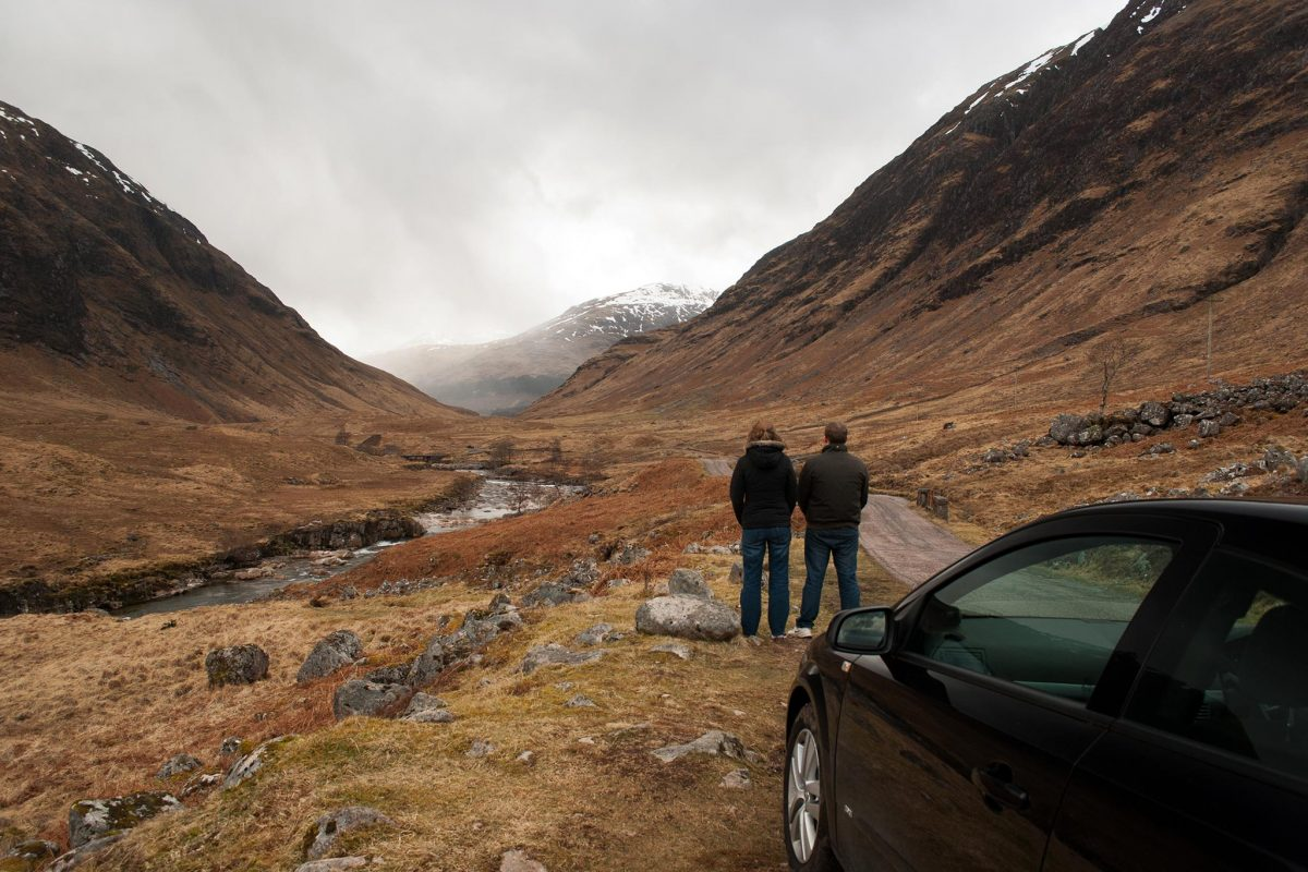 Couple with backs towards to camera posing as Bond and M in the James Bond film. Skyfall. Car in the foreground with the couple in front looking up towards the snow peaked mountains. The sky is moody and grey.