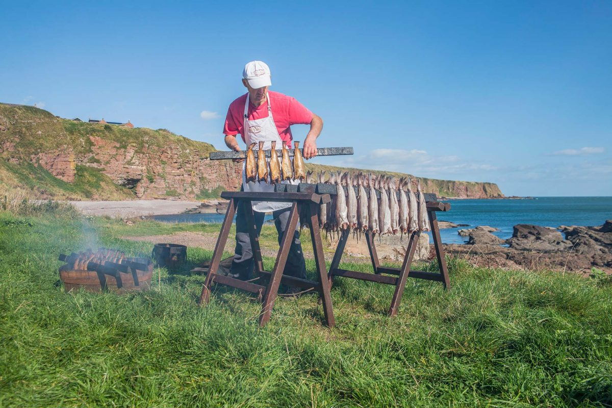 Iain R Spink preparing Arbroath Smokies on the beach at Auchmithie