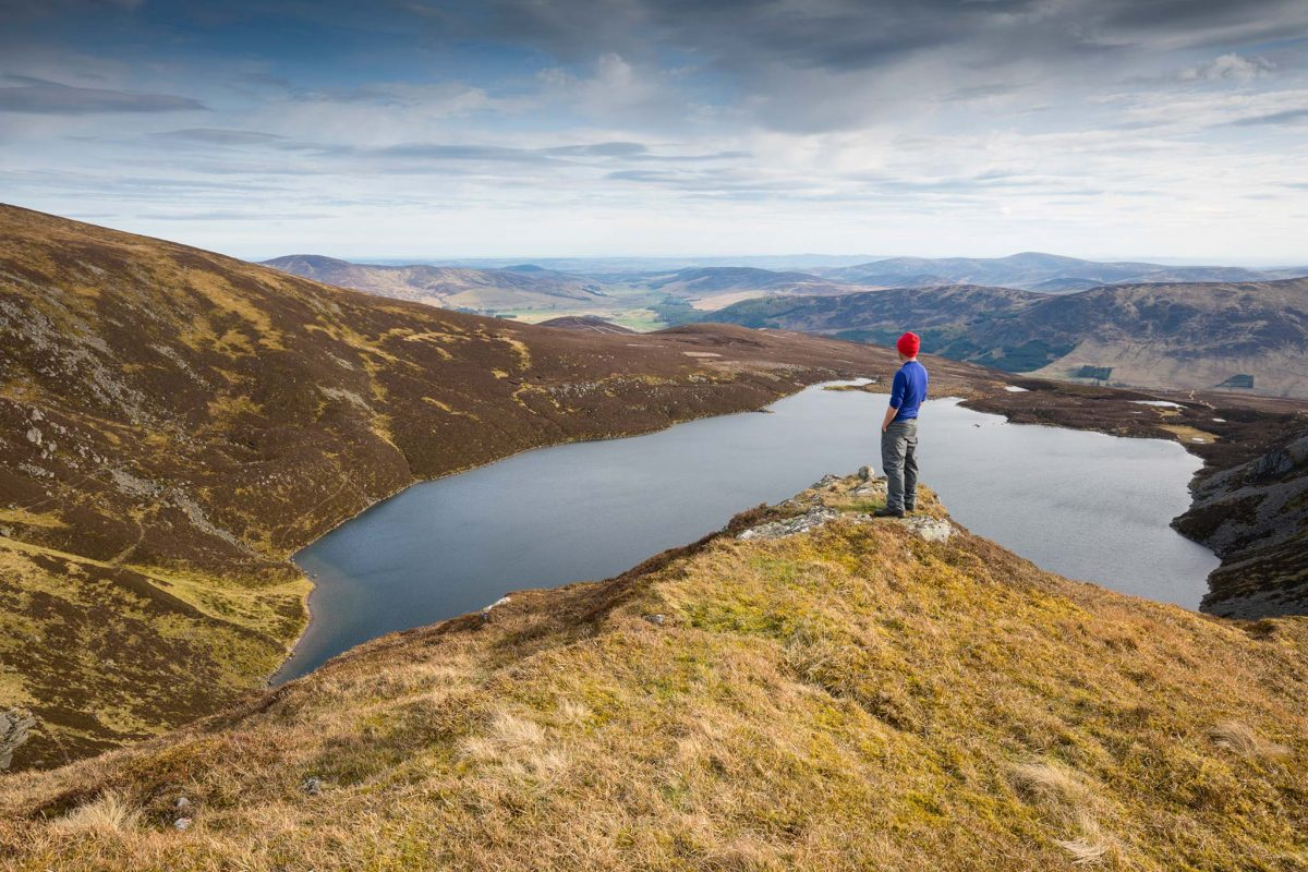 A man stands looking down on Loch Brandy in Glen Clova, Angus Glens