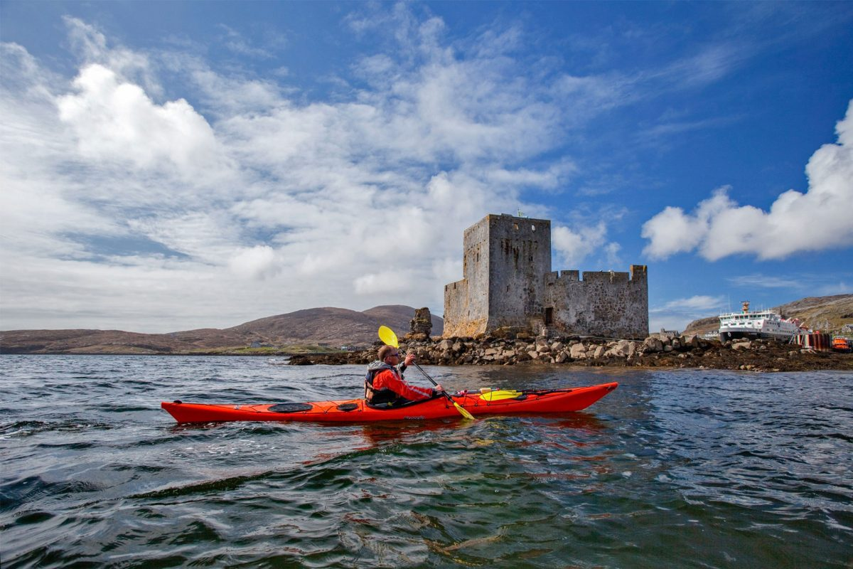 Sea kayaking by Kisimul Castle, Isle of Barra, Outer Hebrides