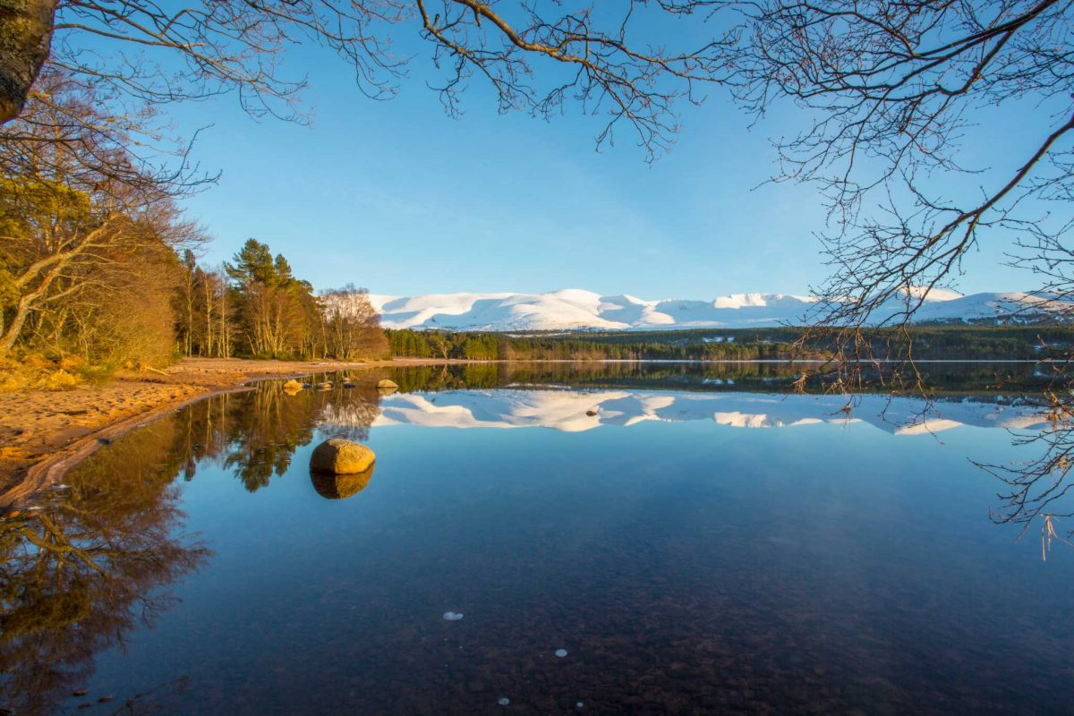 Part of Loch Morlich's beach and views over the loch to the Cairngorm Mountains