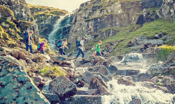 Walkers cross over a natural spring and waterfall, part of the Ben Nevis walking route, Fort William, Highlands