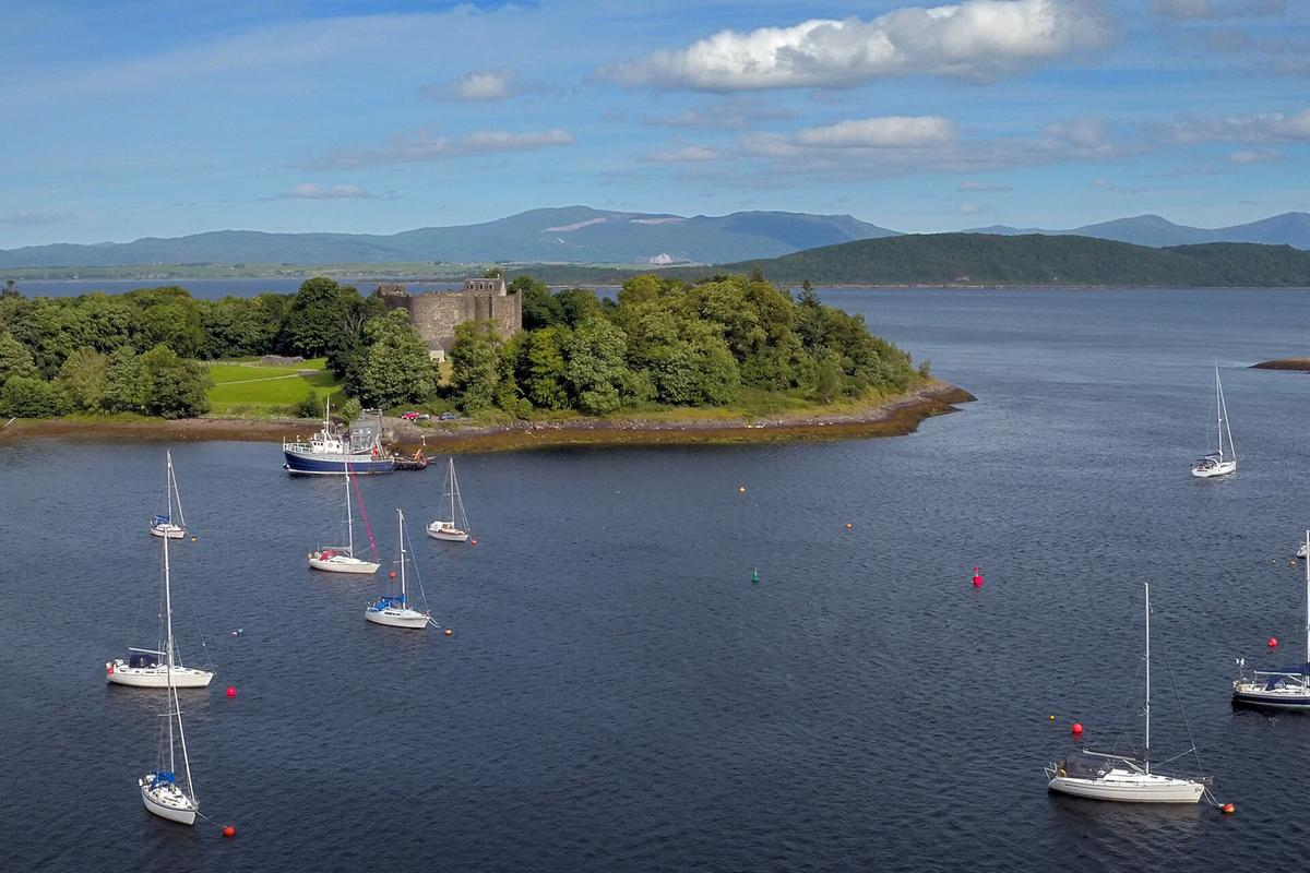Yachts moored in the shadow of historic Dunstaffnage Castle, near Oban