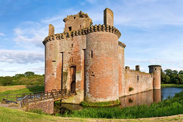 A close look at Caerlaverock Castle and its moat bridge and grass on a bright sunny day © stocksolutions / Dollar Photo Club