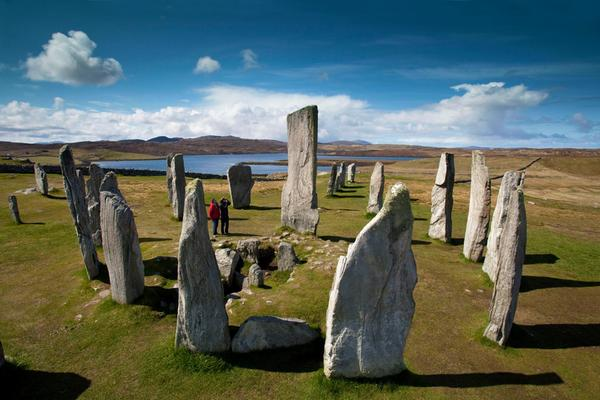 The Calanais Standing Stones are admired by a visiting couple on the Isle of Lewis on a beautiful day