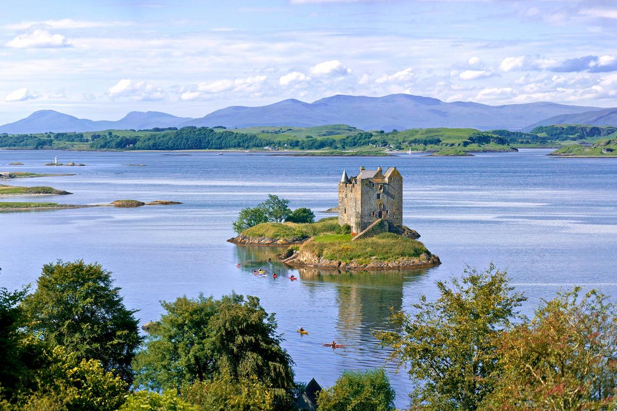 Castle Stalker and Loch Laich surrounding it, with the Isle of Lismore in the background