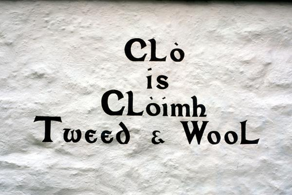 Detail of Gaelic text painted on the white washed wall of a craft shop at Isle Ornsay, Sleat Peninsula, Isle of Skye