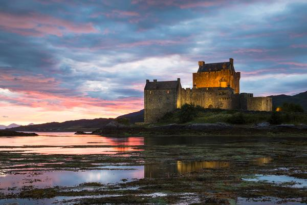 Eilean Donan Castle and Loch Duich at sunset against a blue and pink sky