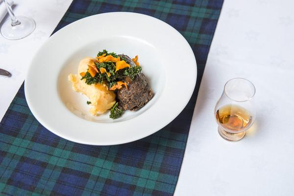 A close up of a dish of haggis, mash and vegetables and a glass of whisky on a tartan tablecloth