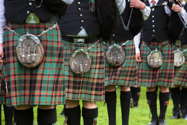 A close up of the pipe band in their red and green tartan kilts at the Forres Vintage Vehicle Day
