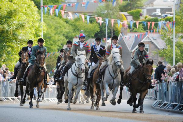 Horses racing through the street during the Selkirk Common Riding, watched by the crowds