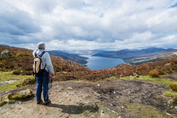 A walker admiring the view on the summit of Ben A'an in The Trossachs