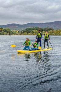 A family tries paddleboarding on Loch Insh, Cairngorms National Park