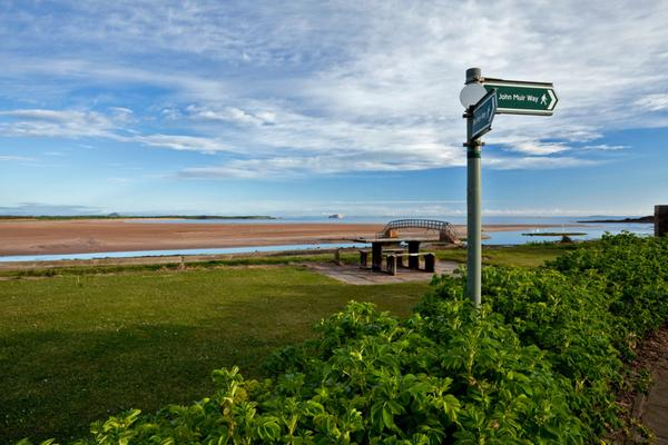 Signpost for the John Muir Way by the footbridge known as 'The Bridge to Nowhere' at Belhaven Bay near Dunbar, East Lothian