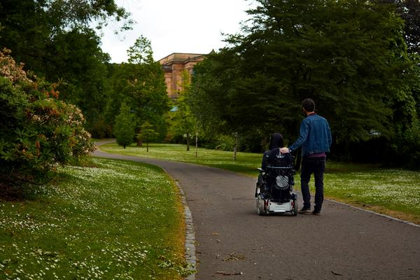 A lady in a wheelchair and her partner enjoy a walk surrounded by greenery