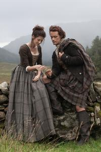 Outlander's Claire and Jamie sitting on a wall © Sony Pictures Television Inc. All Rights Reserved.