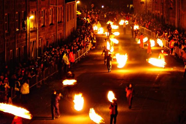 The fireball swingers process through the town as crowds look on.