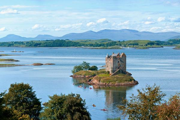 Sea kayakers explore the coastline around Castle Stalker, Loch Laich, Appin, Argyll