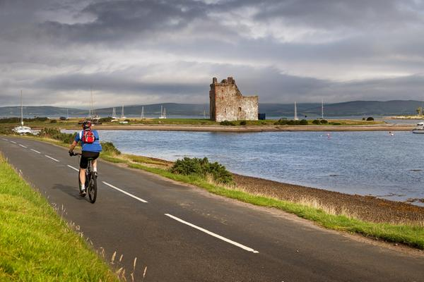 A man cycles past Lochranza Castle, Isle of Arran © istockphoto