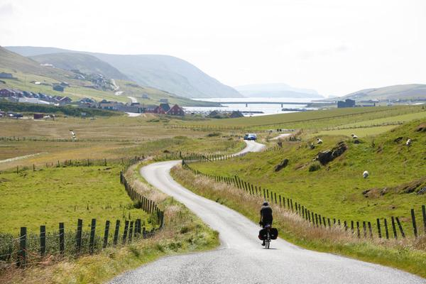 A cyclist rides on the B9074 road between Asta and Scalloway, Shetland