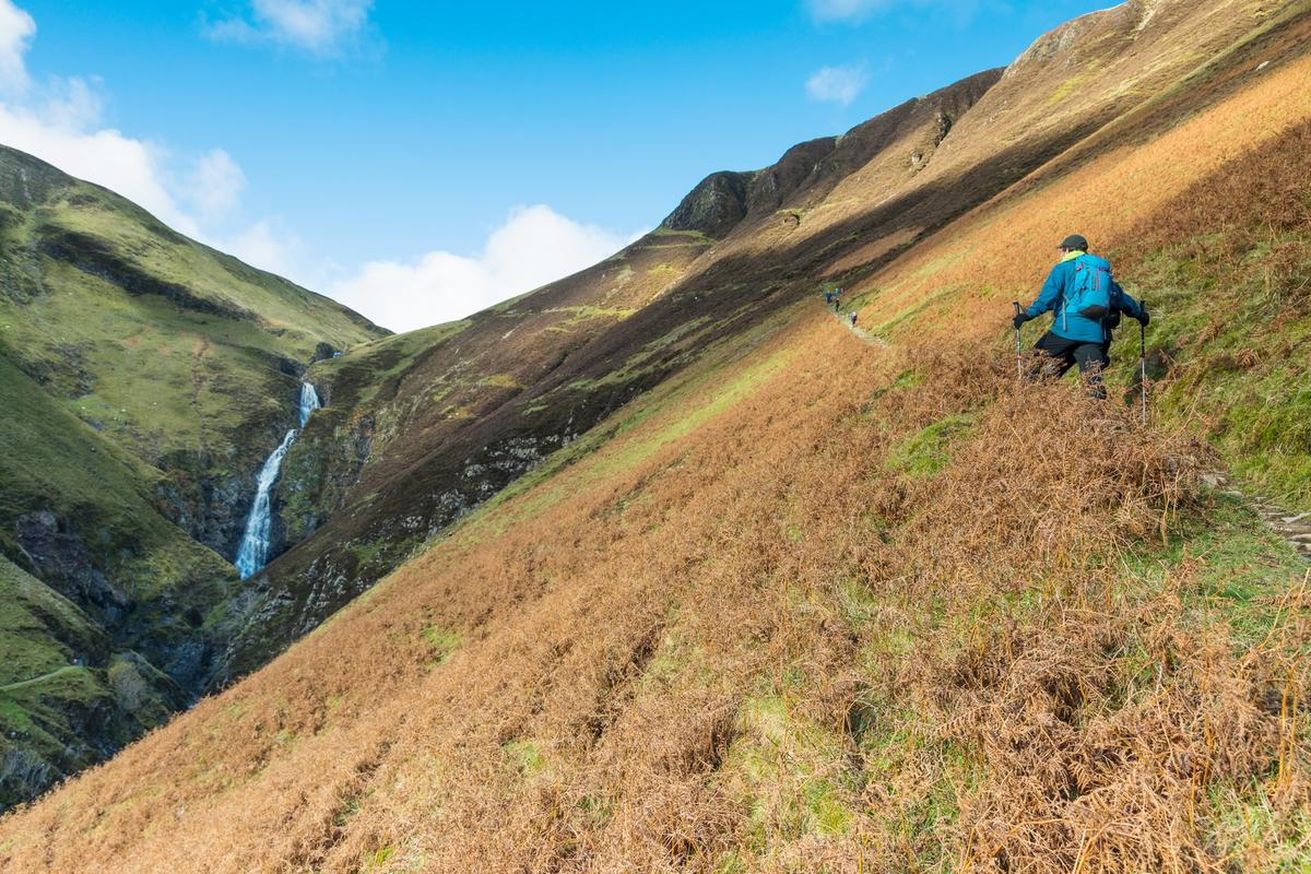Walkers climb the hillside by Grey Mare's Tail, one of the UK's highest waterfalls, in the Moffat Water Valley, Dumfries & Galloway