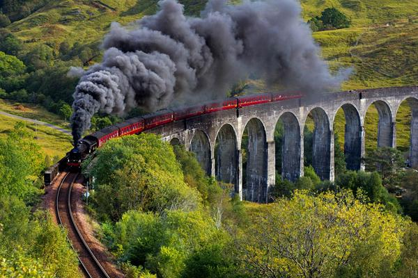A steam train passes over the iconic Glenfinnan viaduct, Highlands