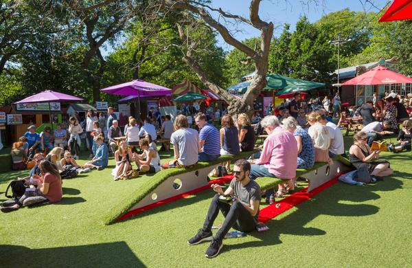 Festival goers sit in the sun at Bristow Square, surrounded by colourful sun parasols and food and drink stalls